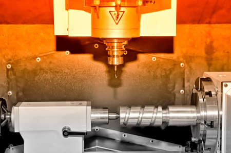 Metal billet is machined on an industrial milling machine.Red toning.