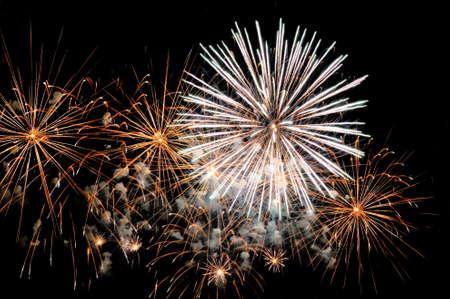 Golden and white fireworks display on dark sky background. Lizenzfreie Bilder