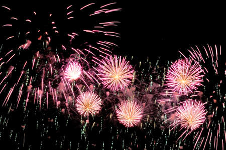 Pink fireworks and scattering of green sparks on dark background.