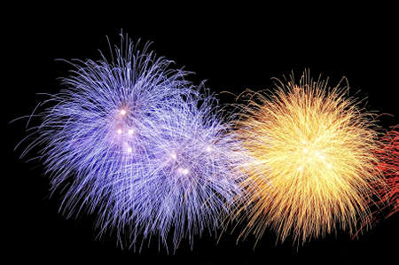 Flashes of fireworks of yellow and blue colors against the black sky.
