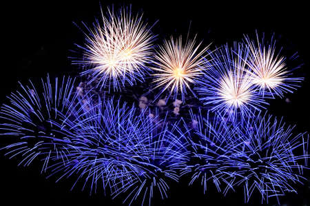Flashes of fireworks of blue and white colors against the black sky background