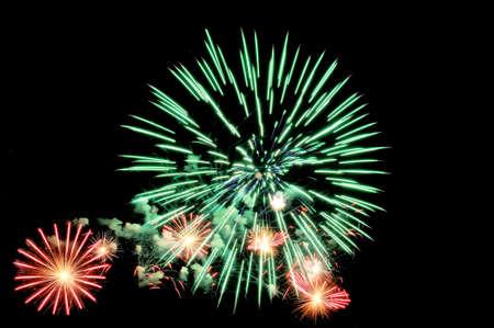 Big green and small red fireworks display on dark sky background Lizenzfreie Bilder