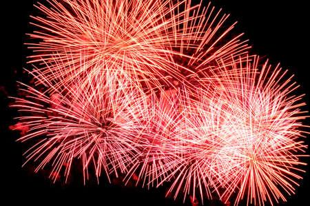 Red fireworks display on dark sky background.