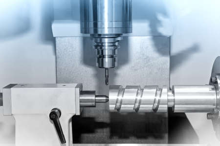 Metal billet is machined on an industrial milling machine.Blue toning.