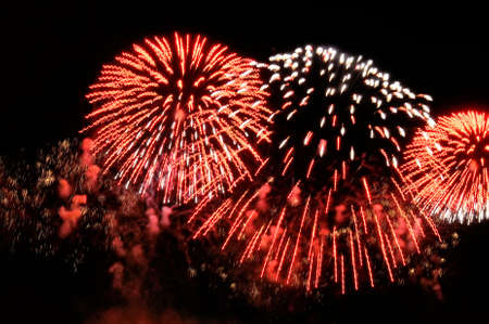 Flashes of fireworks of red and white color against the black sky background