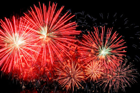 Amazing red fireworks and scattering of blue sparks on dark background.
