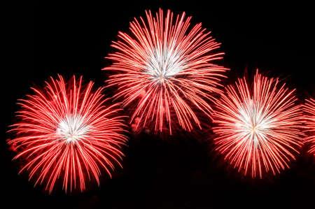 Flashes von Feuerwerkskörpern von roter Farbe gegen den schwarzen Himmel im Hintergrund