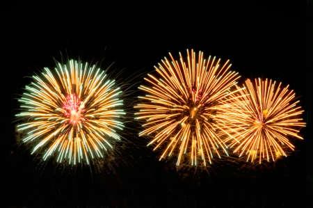 Golden and green salutes fireworks display on dark sky background. Lizenzfreie Bilder