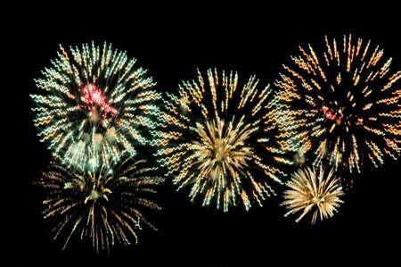 Green and yellow salutes fireworks display on dark sky background Lizenzfreie Bilder