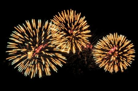 Golden salutes fireworks display on dark sky background.