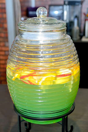 Lemonade of green color with pieces of a citrus in big glass corrugated capacity