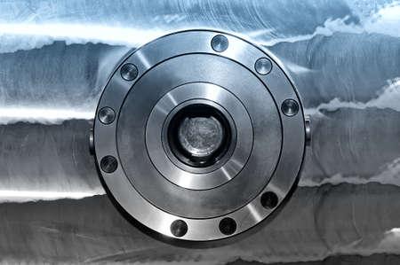 Rundes industrielles Metalldetail über eine Metallplatte. Vorderansicht. Blaue Tönung