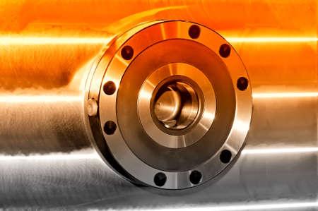 Rundes industrielles Metalldetail über eine Metallplatte. Seitenansicht. Selektive rote Tönung
