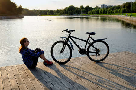Junge Frau in der Sportkleidung, die mit ihren Armen um ihre Knie nahe bei einem Fahrrad auf einem Bretterboden nahe einem Teich sitzt.