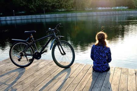 Junge Frau in der Sportkleidung sitzt nahe bei einem Fahrrad auf einem Bretterboden nahe einem Teich. Lizenzfreie Bilder