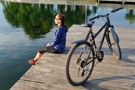 Ein junges Mädchen in der Sportkleidung sitzt nahe bei einem Fahrrad auf einem Bretterboden nahe einem Teich. Seitenansicht Lizenzfreie Bilder