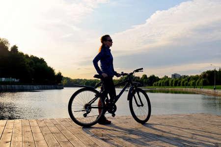 Schattenbild eines sportlichen jungen Mädchens, das mit einem Fahrrad auf einem Bretterboden nahe einem Teich steht