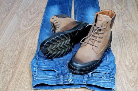 Paar neue hohe Herren Lederstiefel auf blauen klassischen Jeans