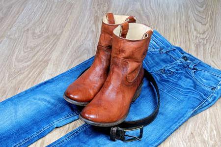 Paar neue klassische Leder braun Cowboy-Stiefel und Leder braun Gürtel auf blauen klassischen Jeans