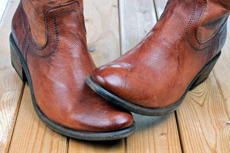 Paare der neuen klassischen ledernen braunen Cowboystiefel auf hölzernen Brettern. Makroaufnahmen