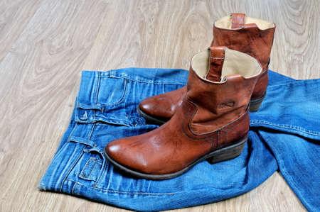 Neue klassische lederne braune Cowboystiefel auf blauen klassischen Jeans