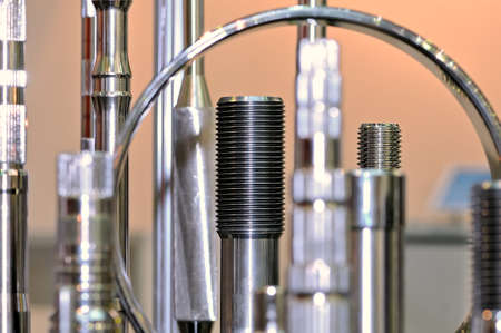 Metal shafts and metallic ring chrome-plated products of different shapes and sizes. Small depth of sharpness