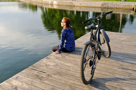 A young girl in sportswear sits next to a bicycle on a wooden floor near a pond. Side view