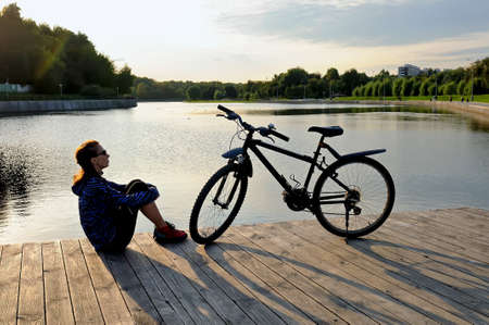 Young woman in sportswear sitting with her arms around her knees next to a bicycle on a wooden floor near a pond.