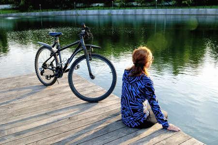 Junge Frau in der Sportkleidung sitzt nahe bei einem Fahrrad auf einem Bretterboden nahe einem Teich. Standard-Bild