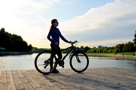 Silhouette of a sporty young girl standing with a bicycle on a wooden floor near a pond
