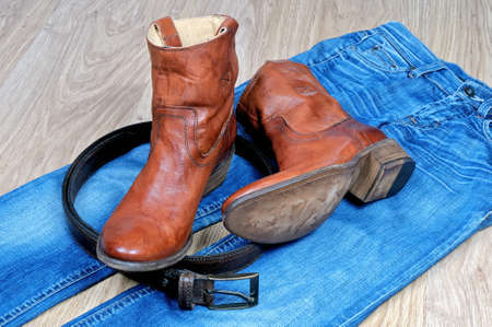 Pair of new classical leather brown cowboy boots and leather brown belt on blue classical jeans