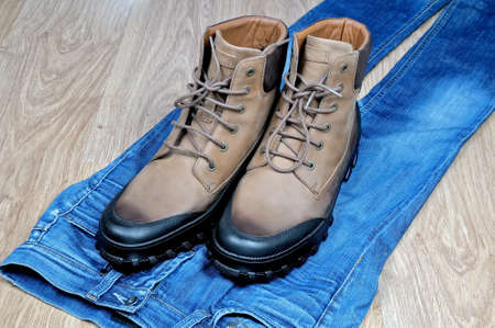 Pair of new high mens leather boots on blue classical jeans Standard-Bild