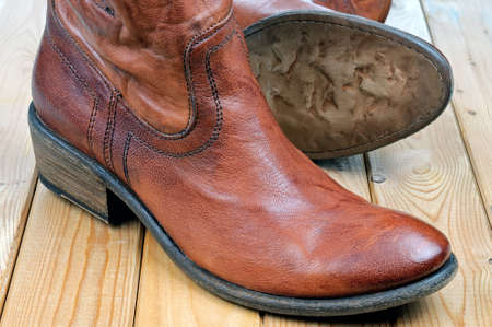 Pair of new classic leather brown cowboy boots on wooden boards. Macro shooting Standard-Bild