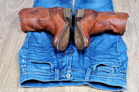 New classical leather brown cowboy boots on blue classical jeans