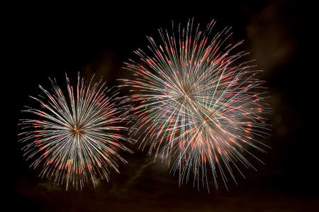 Multi-colored flashes of festive salute fireworks on black sky background