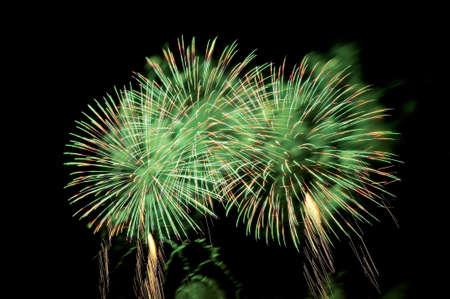 Flashes von Feuerwerkskörpern von grüner Farbe gegen den schwarzen Himmel Standard-Bild
