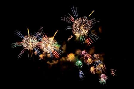 Mehrfarbige Blitze von festlichen Feuerwerk am schwarzen Nachthimmel