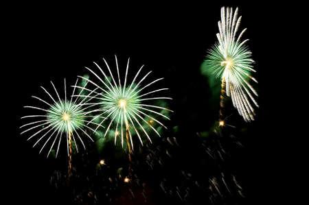 Flashes von Feuerwerk von grünen und weißen Farbe gegen den schwarzen Himmel