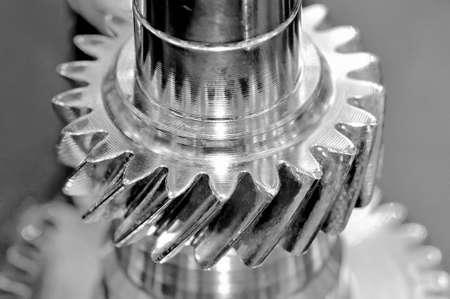 Stahlstange und Zahnrad mit einem Gewinde. Schwarz-Weiß-Tonung, geringe Schärfentiefe. Nahansicht Standard-Bild