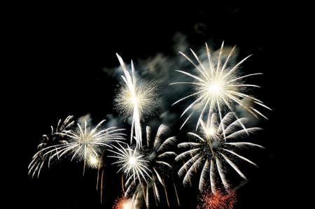 Blitze von Feuerwerken der weißen Farbe gegen den schwarzen Himmel. Standard-Bild