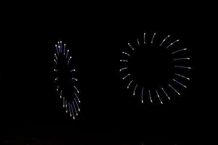 Ein ungewöhnliches Grußfeuerwerk in Form von den Blumenblättern von blauen und weißen Farben im schwarzen nächtlichen Himmel