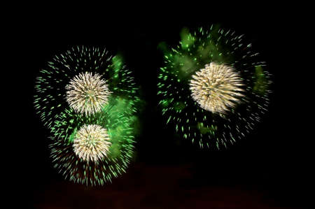 Flashes of fireworks of green and white color against the black sky Standard-Bild