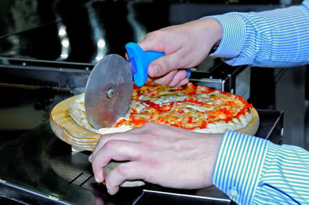 Mens hands cut pizza using a roller knife for pizza