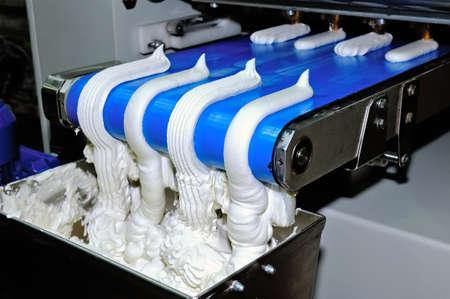 Süßwarenherstellung von Baiser. Die Backmaschine mit dem Förderer, auf dem es Süßwaren gibt