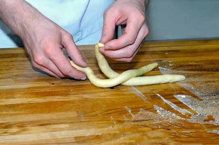 Hände des Kochs auf einem Holztisch machen Süßigkeiten von gerolltem Teig