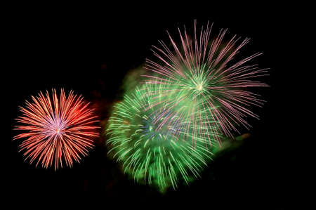 Flashes of fireworks of green, red and purple color against the black sky