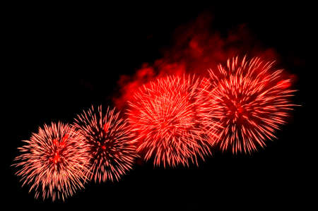 Beautiful festive red fireworks salute on the black sky Standard-Bild