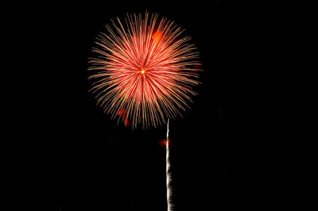 Amazing red fireworks and scattering of gold sparks on dark background.