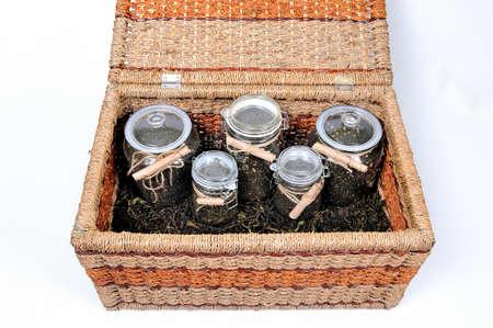 Various glass jars with dry tea leaves of herbal aromatic tea in a wicker basket Standard-Bild