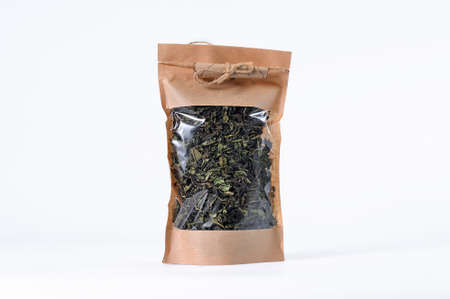 Dry tea leaves of herbal aromatic tea in a gift package with transparent window on a white background